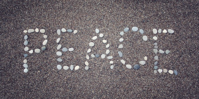 'Peace' word on the sand. Written with pebbles. Aged photo.